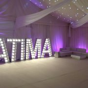 FATIMA in light up letters in a marquee with white hire furniture