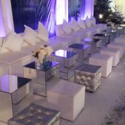 White faux leather sofas and mirror cube table with chesterfield ottomans