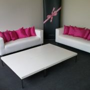 white faux leather sofa with hot pink scatter cushion