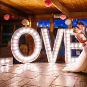 large light up love letters being used at a wedding