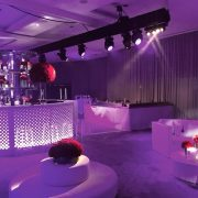 round white daybeds ghost stools and white rattan sofa in night club setting
