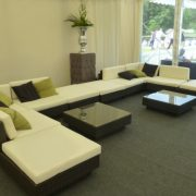 black rattan sofa with green and black scatter cushions