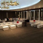 White faux leather sofa and table modules with silver chesterfield ottomans and scatter cushions