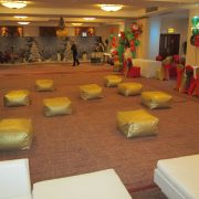 white marrakesh sets with gold prive floor slabs and gold and red scatter cushions with Christmas style decorations in background
