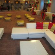 white rattan sofas with gold floor cushions and red and gold scatter cushions