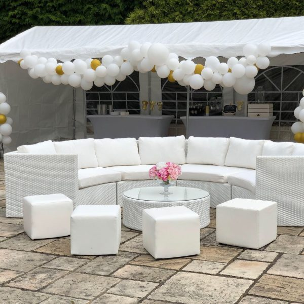 garden furniture hire: white rattan curved sofa with table and white faux leather cubed seating