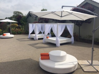 white daybeds and cantilever umbrella