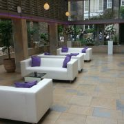 White faux leather club lounge sofas with mirror cubes and purple scatter cushions