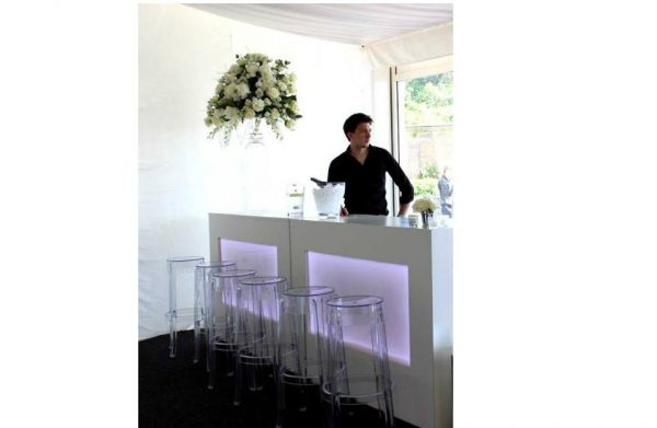 Clear ghost stools at bar at walled garden event