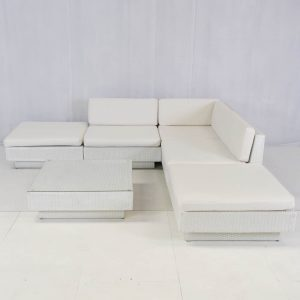 white outdoor rattan sofa modules set up in a l-shape: sofa hire