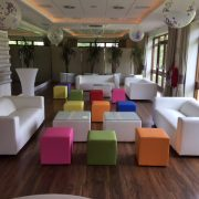 white faux leather sofas with colourful ottoman seating