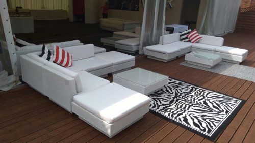 White rattan sofas with red striped scatter cushion
