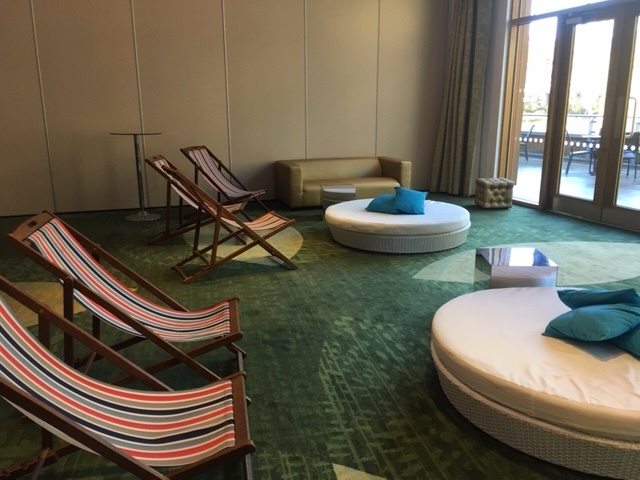 White rattan round daybed with striped deckchairs