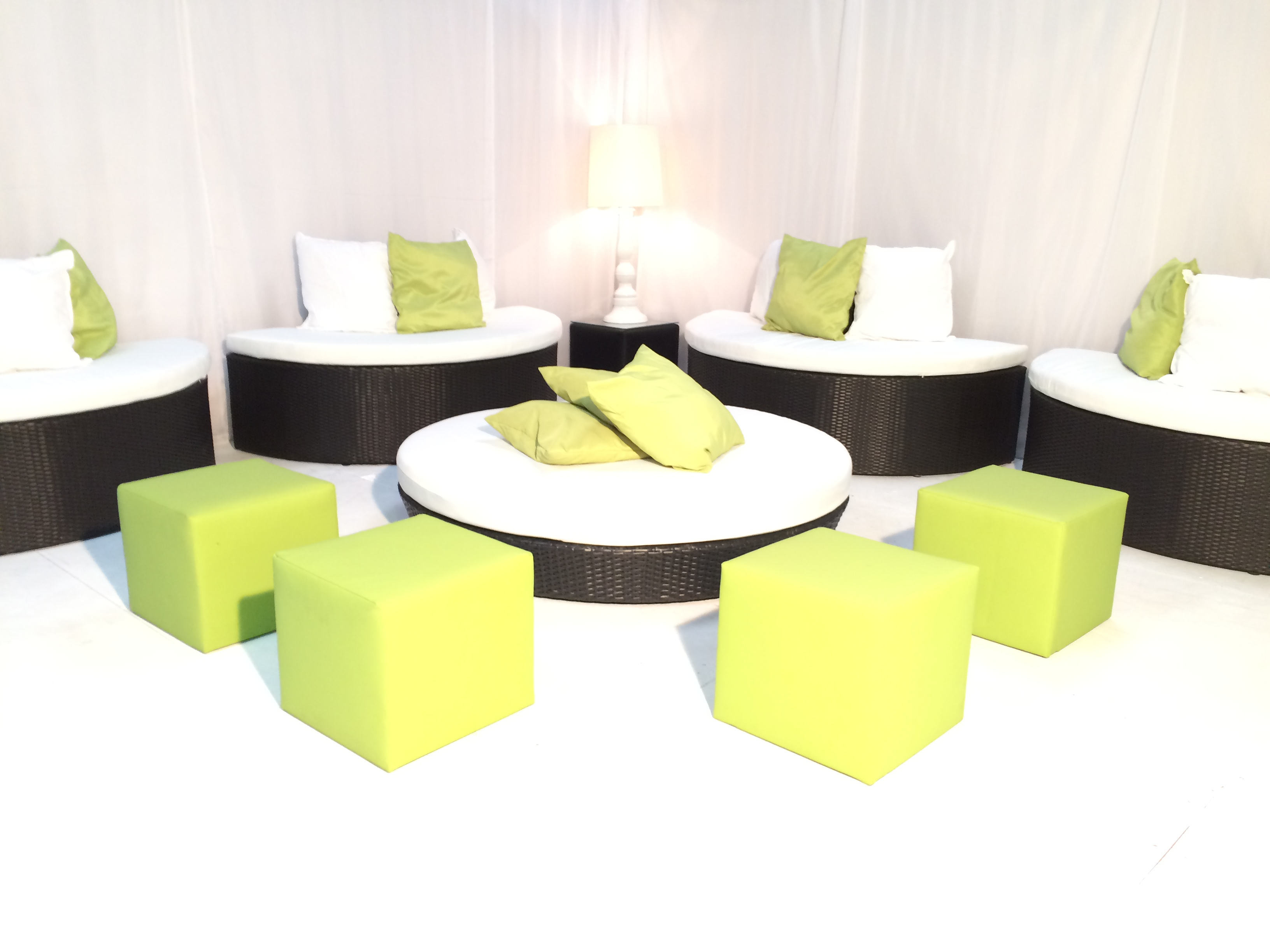Black rattan daybed with lime green cube seats and scatter cushions