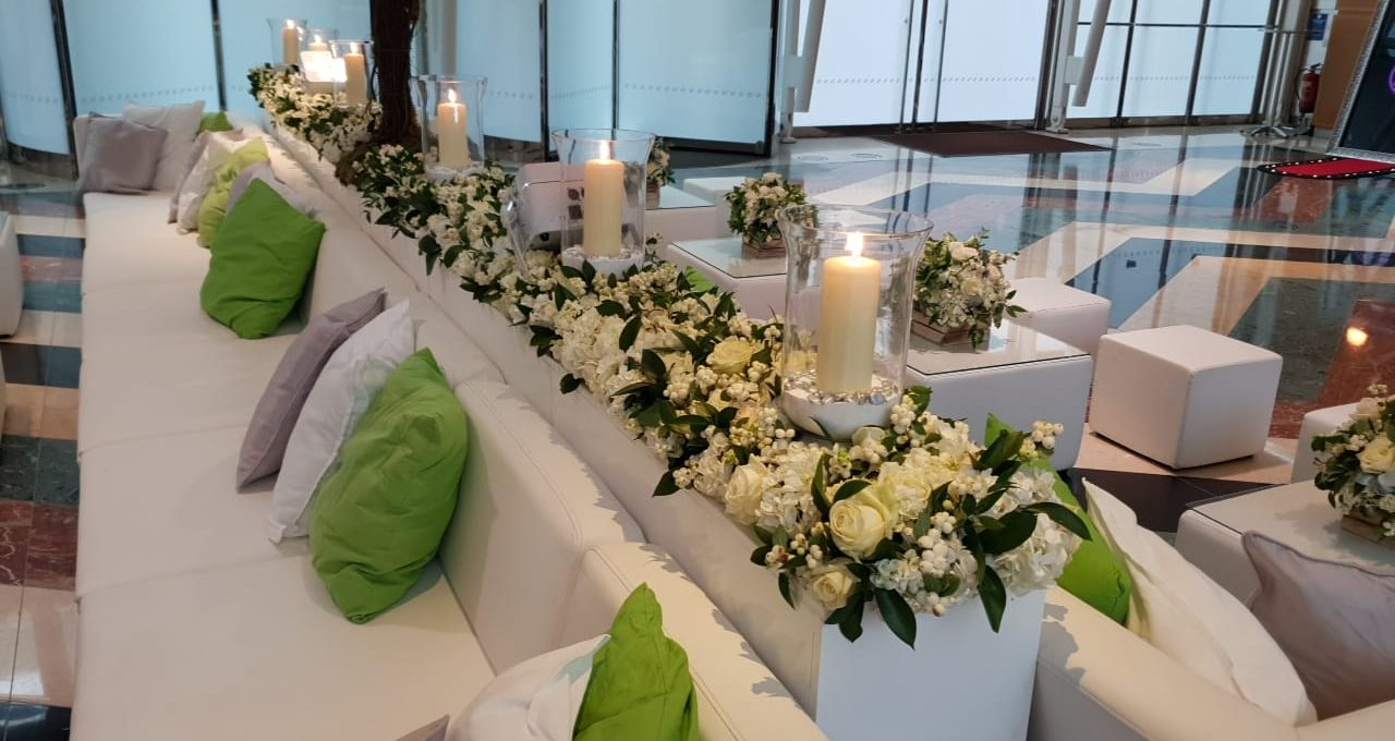 Luxury Wedding Furniture For Hire: white faux leather sofas with flowers, candles, floral decoration, and white ottoman seating