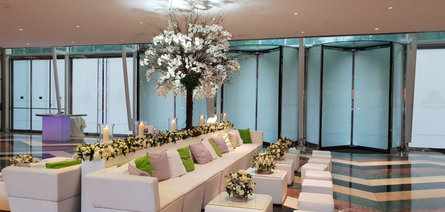 wedding furniture hire: Lobby with revolving doors white faux leather sofas with flowers and candles