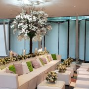 Lobby with revolving doors white faux leather sofas with flowers and candles