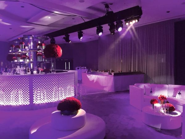 White furniture hire: round white daybeds ghost stools and white rattan sofa in night club setting