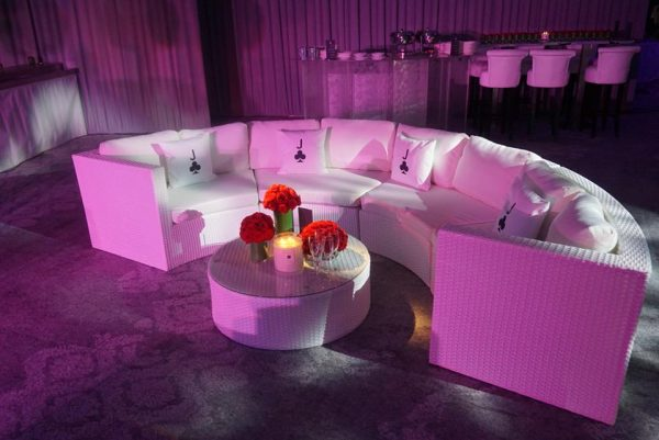 white furniture hire: Bulgari curved sofa with flowers and candle