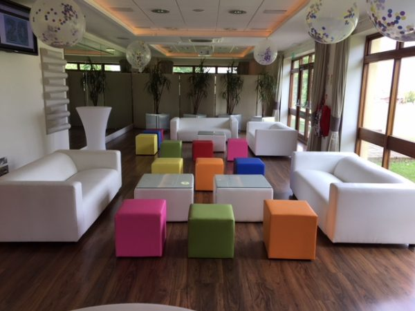 White faux leather sofas with coloured club ottomans