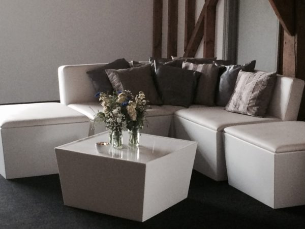 white furniture hire; various seating modules in white placed with silver scatter cushions