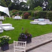 White marrakesh rattan sofas with grey cushions and baby blue scatter cushions at a garden party