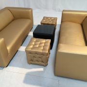 Gold faux leather club sofas with chesterfield gold ottomans and faux leather cabo table with glass top