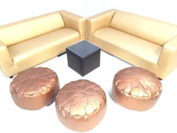 Gold faux leather club sofas with Andaz copper ottomans and a dark faux leather cabo table with glass top