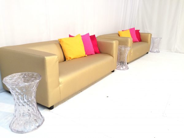 Gold faux leather club sofas with clear ghost tables and coloured scatter cushions