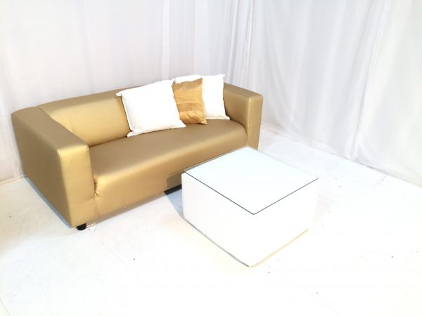 Gold faux leather sofa with gold and white scatter cushions and white faux leather table with glass top