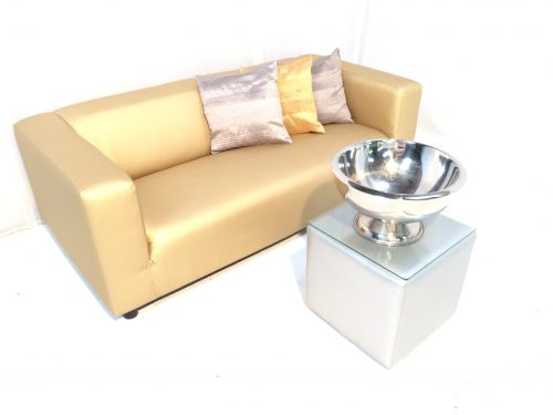 Gold faux leather club sofa with silver faux leather cabo table with glass top and champagne bowl