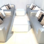 Silver faux leather club lounge sofas with scatter cushions and white cabo tables with glass tops