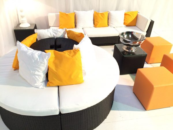 Banyan sofas with orange and white scatter cushions and champagne bowl