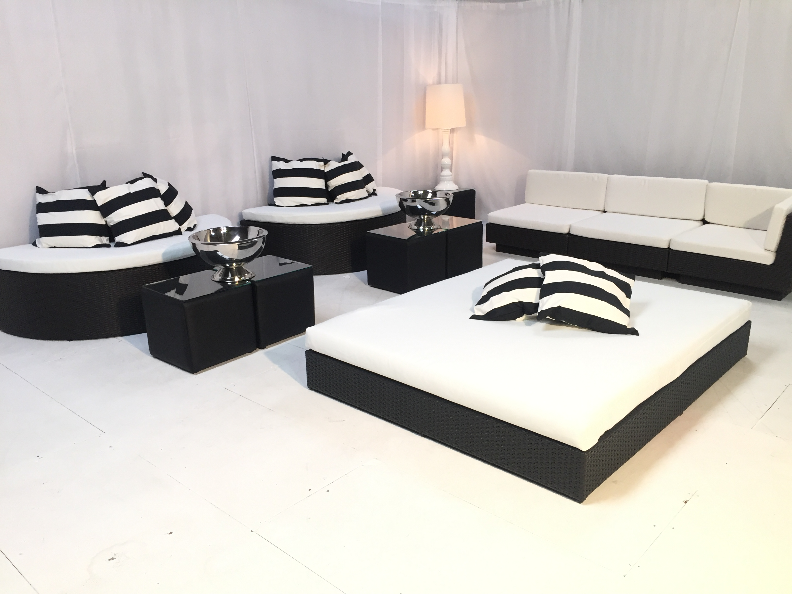Black Rattan Daybed with rattan sofa halves and scatter cushions