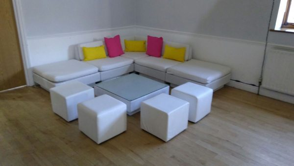 White rattan sofas, white club ottomans, yellow scatter cushions and hot pink scatter cushions
