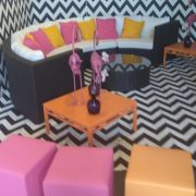 Dark Bulgari sofa in Pop Art style with pink and orange scatter cushions