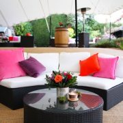Dark Bulgari sections with bright scatter cushions and flowers
