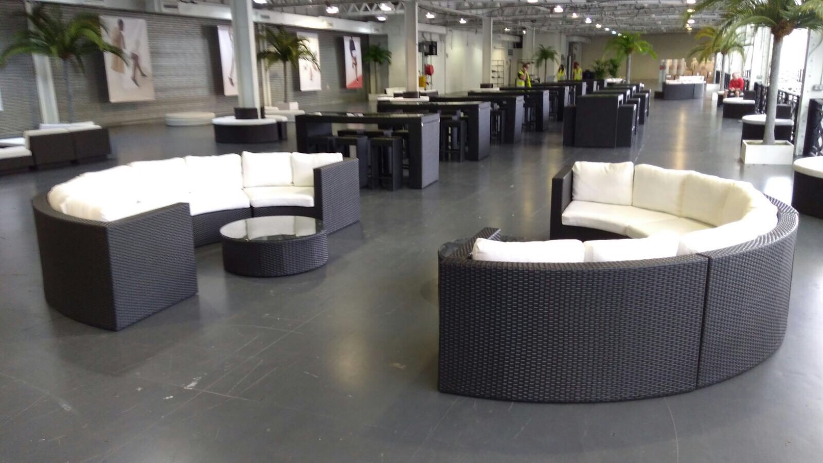 Black rattan sofas at event at Olympia
