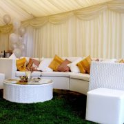 White Rattan Sofa in a marquee with scatter cushions and balloons