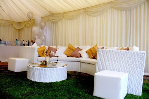 White Rattan Sofa in a marquee with scatter cushions and balloons for wedding furniture hire