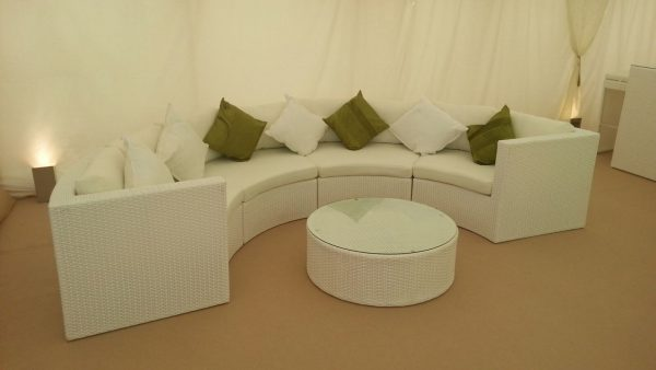 White curved rattan sofa with green and white scatter cushions