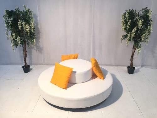 round white daybed with orange scatter cushion