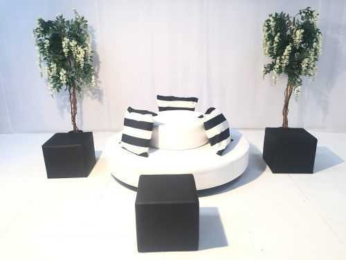 round white daybed with black and white striped scatter cushions and black ottomans
