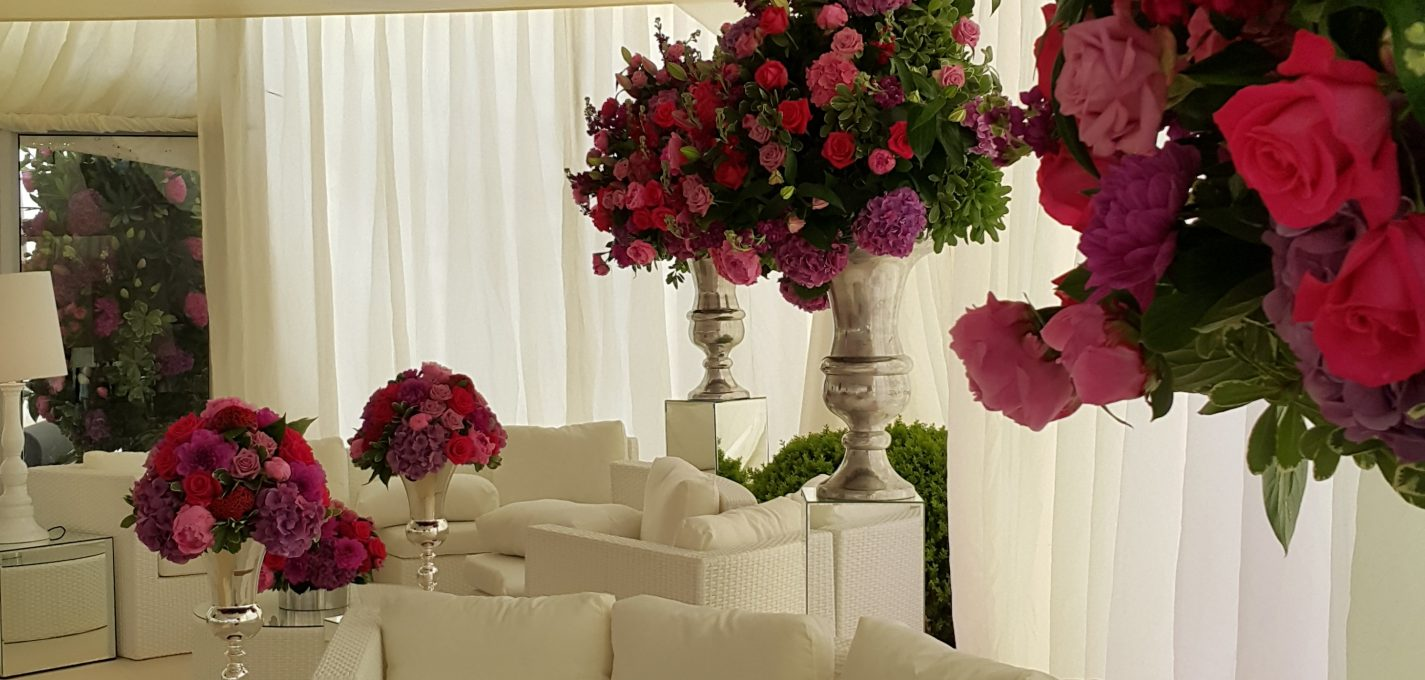 Wedding Marquee Decor For Hire: white semi circular sofas and flowers in marquee