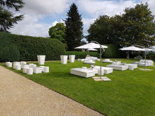 White faux leather Chesterfield Benches on grass with outdoor Cantilever Umbrellas