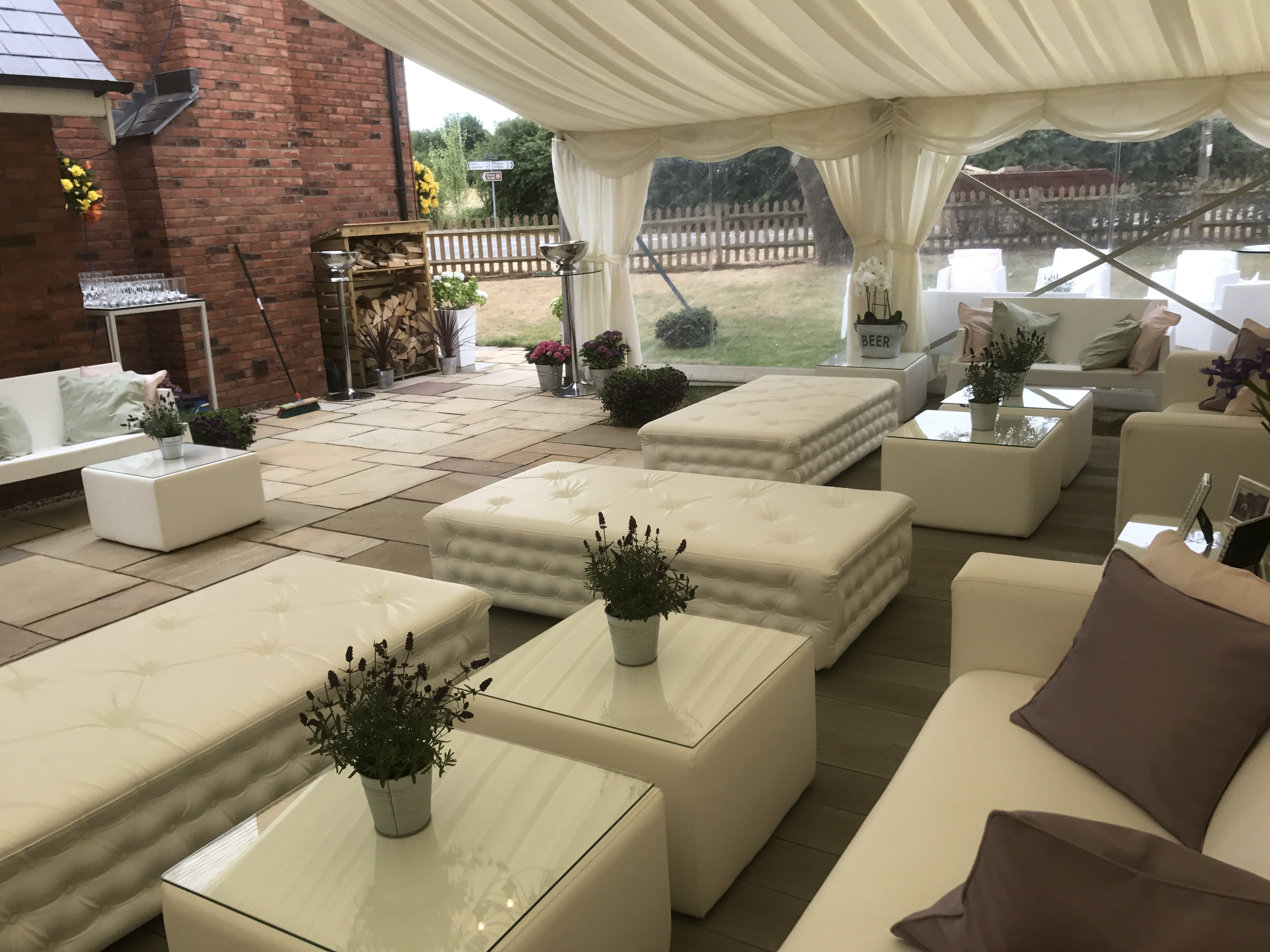 White faux leather Chesterfield Benches with matching tables and flowers in marquee