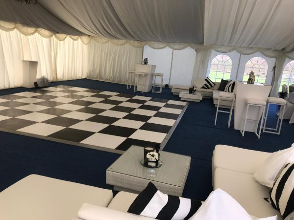 white poseur tables in marquee with black and white checked dance floor