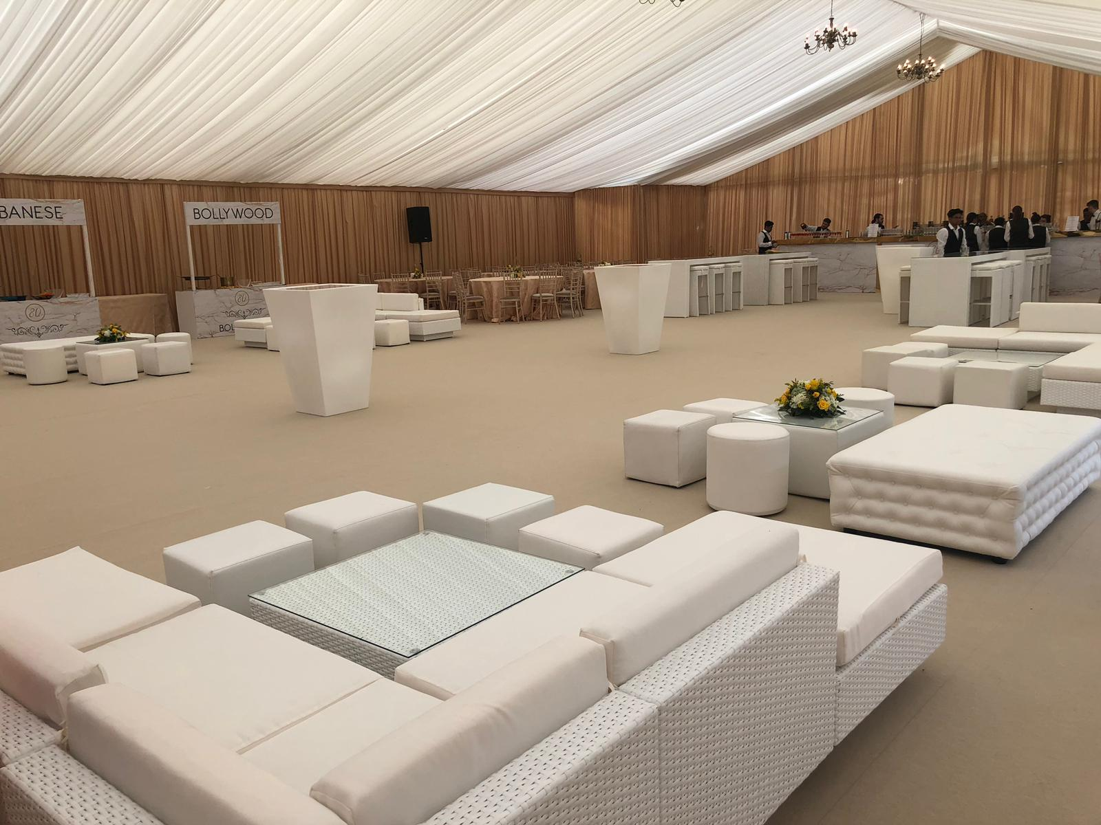 white rattan sofas with matching table, white faux leather cubed seating, white faux leather rounded seating, white faux leather bench, tall white poseur tables, white rattan tables and stools at party in marquee