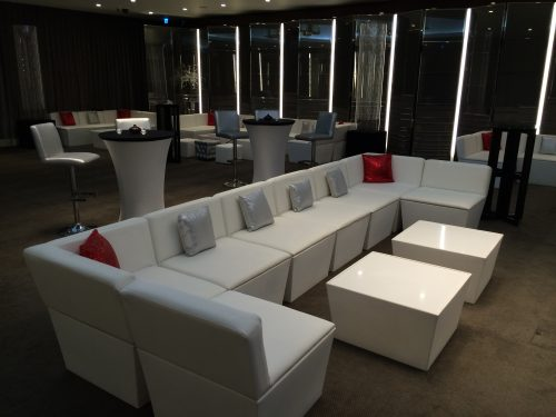 faux leather sofa in white and table modules with silver chesterfield ottomans and mandalay stools