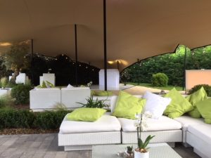 white furniture in outdoor marquee area with white and green cushions